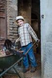 Criança com um carrinho de mão com um gato Fotografia de Stock