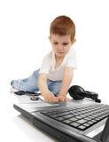 A criança com um computador pessoal Fotografia de Stock