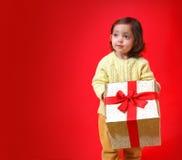 Criança com um presente do Natal Fotos de Stock Royalty Free