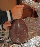 Criança com um punho que quebra o ovo da páscoa feito do chocolate Imagens de Stock