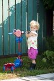A criança com um skate nas botas de borracha imagens de stock royalty free