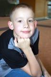 A criança com um sorriso com um ar pensativo Imagens de Stock Royalty Free