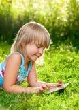 Criança com um tablet pc exterior Imagens de Stock Royalty Free