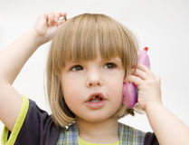 Criança com um telefone do brinquedo Fotografia de Stock Royalty Free