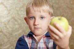 Criança com uma maçã em suas mãos Menino de olhos azuis pequeno louro Fotos de Stock