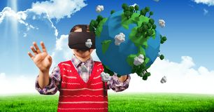 Criança com vidros virtuais atrás de uma terra 3D com fundo do céu Imagens de Stock Royalty Free