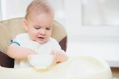 A criança come as mãos do papa de aveia da placa Imagem de Stock