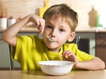 A criança come de um copo branco imagens de stock royalty free