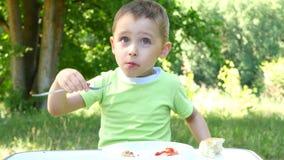 A criança come o assado, sentando-se na tabela no fundo da floresta verde video estoque