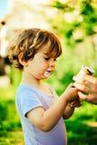 A criança come o gelado em um dia de verão na máscara de uma árvore Fotografia de Stock Royalty Free