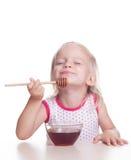 A criança come o mel Imagens de Stock Royalty Free