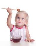 A criança come o mel Fotografia de Stock Royalty Free