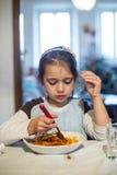 A criança come os espaguetes imagens de stock