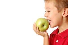 A criança come uma maçã Fotos de Stock Royalty Free