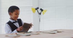 Criança como o executivo empresarial que usa a tabuleta digital 4k video estoque