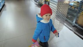 A criança compra o comida para bebê em uma loja ou em um supermercado video estoque