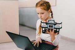 criança concentrada bonita que programa o robô diy, haste imagem de stock