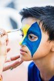 Criança considerável do menino de nove anos nova tendo sua cara pintada para o divertimento em uma festa de anos Foto de Stock Royalty Free