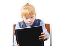 A criança considera o livro Foto de Stock Royalty Free
