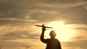 A criança corre no sol com um avião em sua mão Silhueta das crianças que jogam no plano Menina que joga com a video estoque