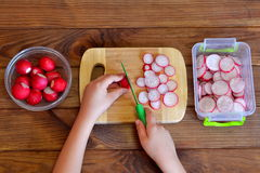 A criança corta vegetais para a salada usando a faca de cozinha As crianças entregam guardar uma faca e um rabanete Vegetais para foto de stock