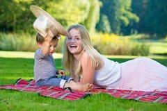 Criança curiosa que levanta acima do chapéu quando a mulher rir foto de stock royalty free