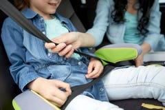 Criança da asseguração da mulher com o cinto de segurança da segurança no carro imagem de stock royalty free