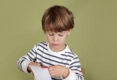 A criança da atividade das artes e dos ofícios das crianças que aprende cortar com Scissor Fotografia de Stock