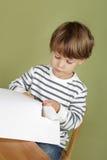 A criança da atividade das artes e dos ofícios das crianças que aprende cortar com Scissor Fotos de Stock Royalty Free