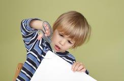 A criança da atividade das artes e dos ofícios das crianças que aprende cortar com Scissor Fotos de Stock