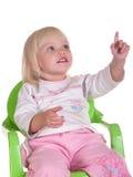 A criança da beleza senta-se na cadeira fotografia de stock royalty free