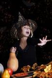 Criança da bruxa com a abóbora que faz a mágica no Dia das Bruxas Foto de Stock Royalty Free