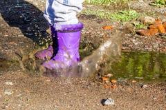 Criança da caminhada do verão nas botas de borracha em uma poça Foto de Stock