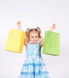 Criança da compra Sacos de compra da terra arrendada da menina Imagem de Stock Royalty Free