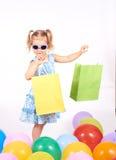 Criança da compra Sacos de compra da terra arrendada da menina Fotografia de Stock