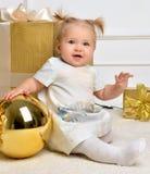 Criança da criança do bebê do Natal perto dos presentes e dos vagabundos de Natal do ouro Fotos de Stock Royalty Free