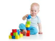 Criança da criança que joga com brinquedos do bloco de apartamentos imagem de stock