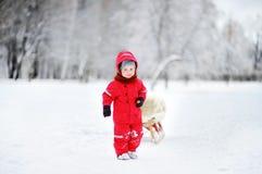Criança da criança que monta um pequeno trenó Jogo de crianças fora na neve foto de stock royalty free