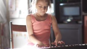 A criança da criança de 6 anos aprende jogar o piano a menina bonito pequena está jogando um sintetizador em casa video estoque