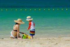 Criança da criança de dois anos que joga com a mãe na praia Fotos de Stock Royalty Free