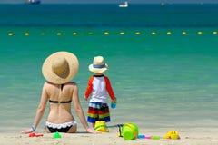 Criança da criança de dois anos que joga com a mãe na praia Foto de Stock