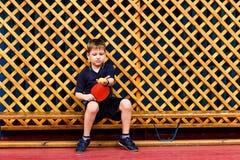 A criança da criança de sete anos senta-se no banco com uma raquete de tênis imagens de stock royalty free