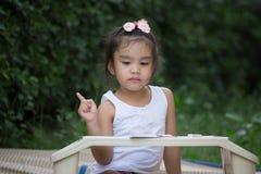 Criança da escola primária que pensa sobre a resposta que senta-se em sua mesa foto de stock