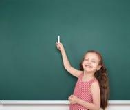 Criança da estudante no ponto listrado vermelho do vestido e desenho no fundo verde do quadro, conceito das férias da escola de v Foto de Stock