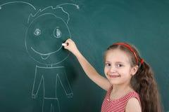 Criança da estudante no vestido listrado vermelho que tira o homem feliz no fundo verde do quadro, conceito das férias da escola  Imagem de Stock