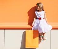 Criança da forma da rua, menina bonita no vestido com saco da loja Fotos de Stock Royalty Free