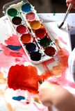 A criança da foto pinta uma escova com pinturas do mel da aquarela mãos pequenas na pintura vermelha fotos de stock royalty free