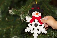 A criança da mão toma a decoração do Natal Foto de Stock Royalty Free