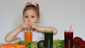 A criança da menina bebe os batidos vegetais - cenoura, beterraba e verde detox vídeos de arquivo