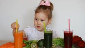 A criança da menina bebe os batidos vegetais - cenoura, beterraba e verde detox filme